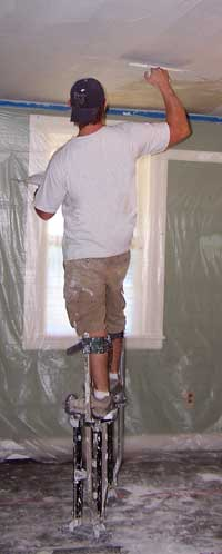 Troweling plaster during resurfacing a ceiling.  Avalanche Plastering